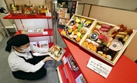 A sales assistant shows a sample of an osechi set of traditional New Year's delicacies at the Matsuya Ginza department store in Chuo Ward, Tokyo, on Dec. 18. Almost all sets have been sold out. (The Yomiuri Shimbun)