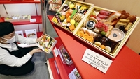 A sales assistant shows a sample of an osechi set of traditional New Year's delicacies at the Matsuya Ginza department store in Chuo Ward, Tokyo, on Dec. 18. MUST CREDIT: Japan News-Yomiuri