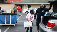 Fernaly Nazaire, 7, brings donated food to cars at the Seasons Florida Resort in Kissimmee. MUST CREDIT: Photo by Eve Edelheit for The Washington Post.