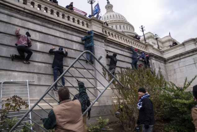 Trump supporters scale the walls on the Senate side of the Capitol on Wednesday, Jan. 6, 2021. MUST CREDIT: Washington Post photo by Michael Robinson Chavez