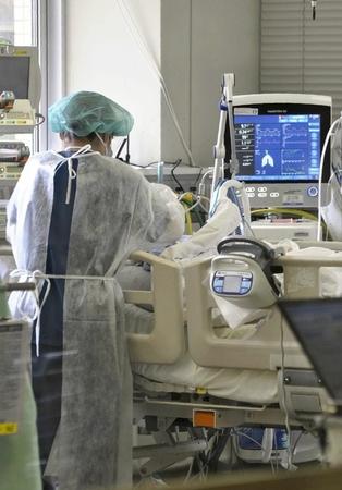 A nurse provides care to a patient infected with the novel coronavirus at a hospital in Fukuoka on Dec. 23, 2020. (The Yomiuri Shimbun)