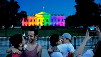 Kelly Miller, left, and her wife, Lindsey Miller, center, embrace on June 26, 2015, outside the White House, lighted in multicolored lights in recognition of the Supreme Court's decision to legalize same-sex marriage in all 50 states. The Millers were married two years ago in Washington State, where same-sex marriage was legalized. MUST CREDIT: Washington Post photo by Michael S. Williamson