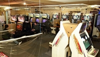 The last few customers are seen on Saturday in Game Spot 21 in Shinjuku Ward, Tokyo. The arcade had been outfitted with plastic sheets as a preventive measure against the coronavirus. MUST CREDIT: Japan News-Yomiuri