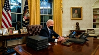 President Biden picks up a pen in the Oval Office to sign a raft of executive orders, including one that repealed his predecessor's Muslim travel ban, on Jan. 20. MUST CREDIT: Washington Post photo by Jabin Botsford.