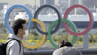 A man wearing a protective mask, left, stands in front of Olympic rings installed in Tokyo on March 11, 2020. MUST CREDIT: Bloomberg photo by Kiyoshi Ota.