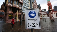 A protective face mask sign in Romerberg Square in Frankfurt, on Jan. 29. MUST CREDIT: Bloomberg photo by Alex Kraus.