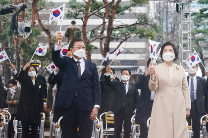 President Moon Jae-in and first lady Kim Jung-sook wave the Korean flag at a ceremony marking the 102nd anniversary of the March 1 Independence Movement in Seoul on Monday. (Cheong Wa Dae)
