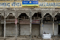 A man sits outside shuttered stores in New Delhi on Aug. 31, 2020. MUST CREDIT: Bloomberg photo by Anindito Mukherjee.