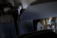 Passengers wear protective masks sit on a Boeing Co. 737-800 during an American Airlines Group Inc. flight departing from Los Angeles International Airport (LAX). Photographer: Patrick T. Fallon/Bloomberg