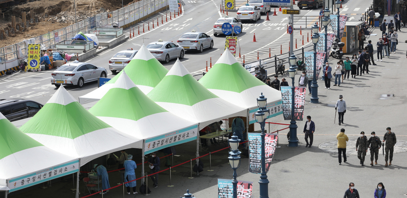 This photo, taken on Friday, shows citizens waiting in line to receive COVID-19 tests at a makeshift testing site set up in front of Seoul Station. (Yonhap)