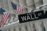A Wall Street street sign outside the New York Stock Exchange as snow falls in New York on Feb. 1, 2021. MUST CREDIT: Bloomberg photo by Jeenah Moon.