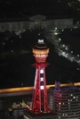 """Tsutenkaku Tower is lit up in red in Osaka City on Wednesday after the Osaka prefectural government signaled a """"red light,"""" the emergency level under its own coronavirus warning system. (The Yomiuri Shimbun)"""