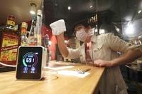 A CO2 sensor, left, and a tall plexiglass partition are set up at a bar in Shibuya Ward, Tokyo, on Thursday. (The Yomiuri Shimbun)