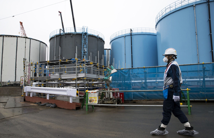 An employee passes storage tanks for contaminated water at Tokyo Electric Power Co.'s Fukushima Dai-ichi nuclear power plant in Okuma, Fukushima, Japan, on Feb. 23, 2017. MUST CREDIT: Bloomberg photo by Tomohiro Ohsumi