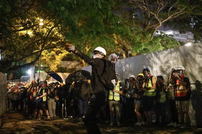 A protester hurls a brick into the Tsim Sha Tsui police station, Hong Kong, Aug 3, 2019. (PHOTO / CHINA DAILY)