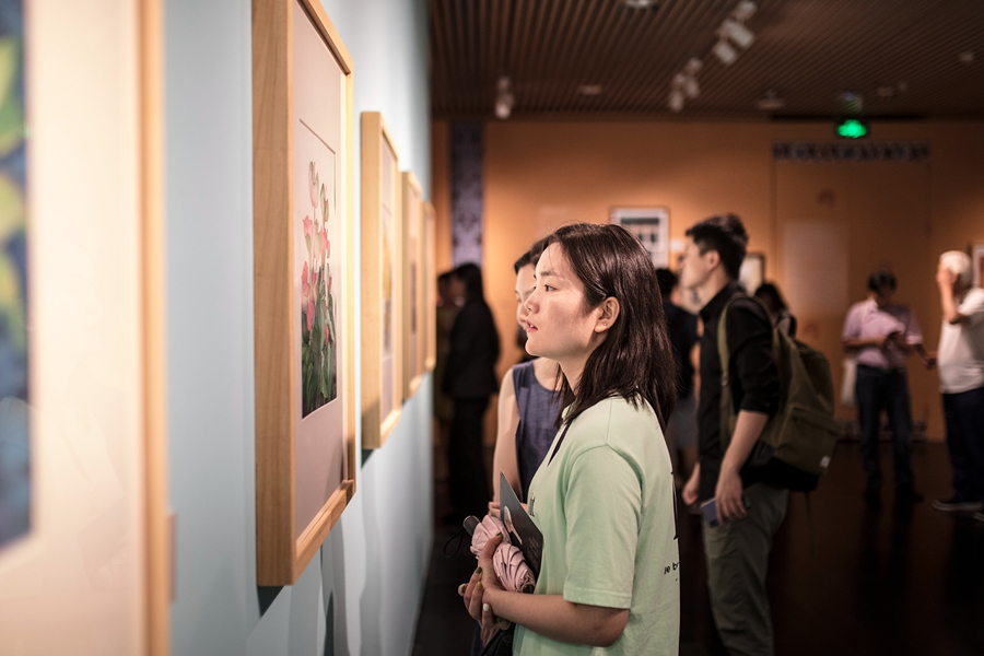 A visitor looks at a flora-themed painting by Chang Shana in Everlasting Beauty of Dunhuang, an exhibition of her and her late father Chang Shuhong's artworks at the Tsinghua University Art Museum through Sept 15.[Photo provided to China Daily]