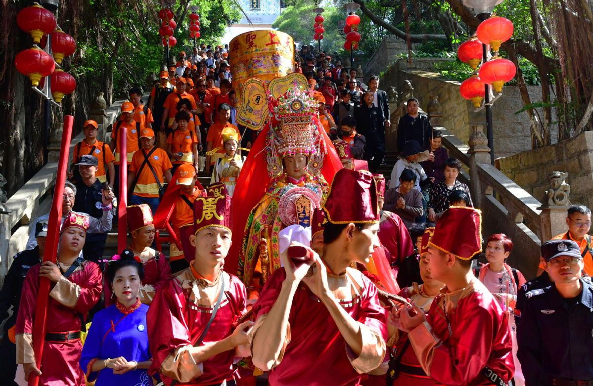 Followers carry the statue of the goddess Mazu as it leaves the Meizhou Mazu Ancestral Temple on Meizhou Island, Fujian province, for its journey to Thailand on Nov 13. [Photo/Xinhua]