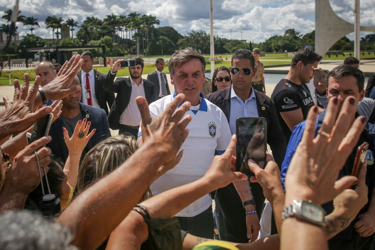 Brazilian President Jair Bolsonaro greets supporters during a demonstration outside of the Planalto Palace in Brasilia, Brazil, on March 15, 2020. MUST CREDIT: Bloomberg photo by Andre Coelho