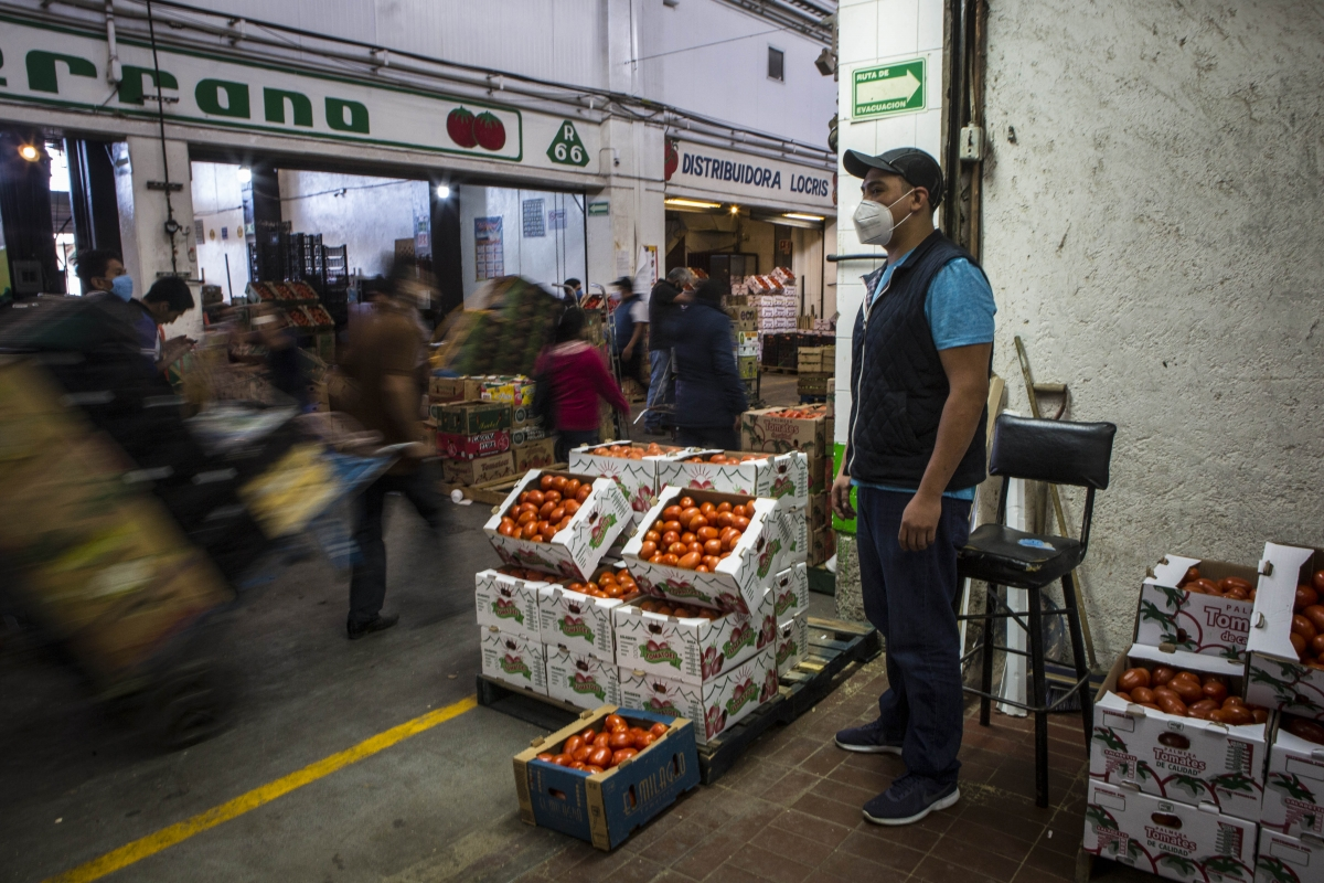 Carlos Molina, 31, whose father, Martin Mateo, 50, died of covid-19,, stands at the entrance of his family's tomato stall at the Central de Abastos in Mexico City on June 12, 2020. MUST CREDIT: Photo for The Washington Post by Jane Hahn