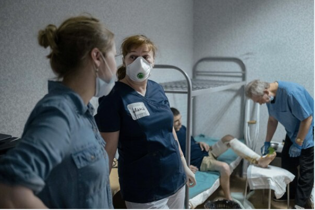 Lana Zhurkina, right, talks to a social worker while providing a medical help for a men living in one of the hostels organized by Dom Druzei (House of Friends) in Moscow on June 24, 2020. MUST CREDIT: Photo for The Washington Po