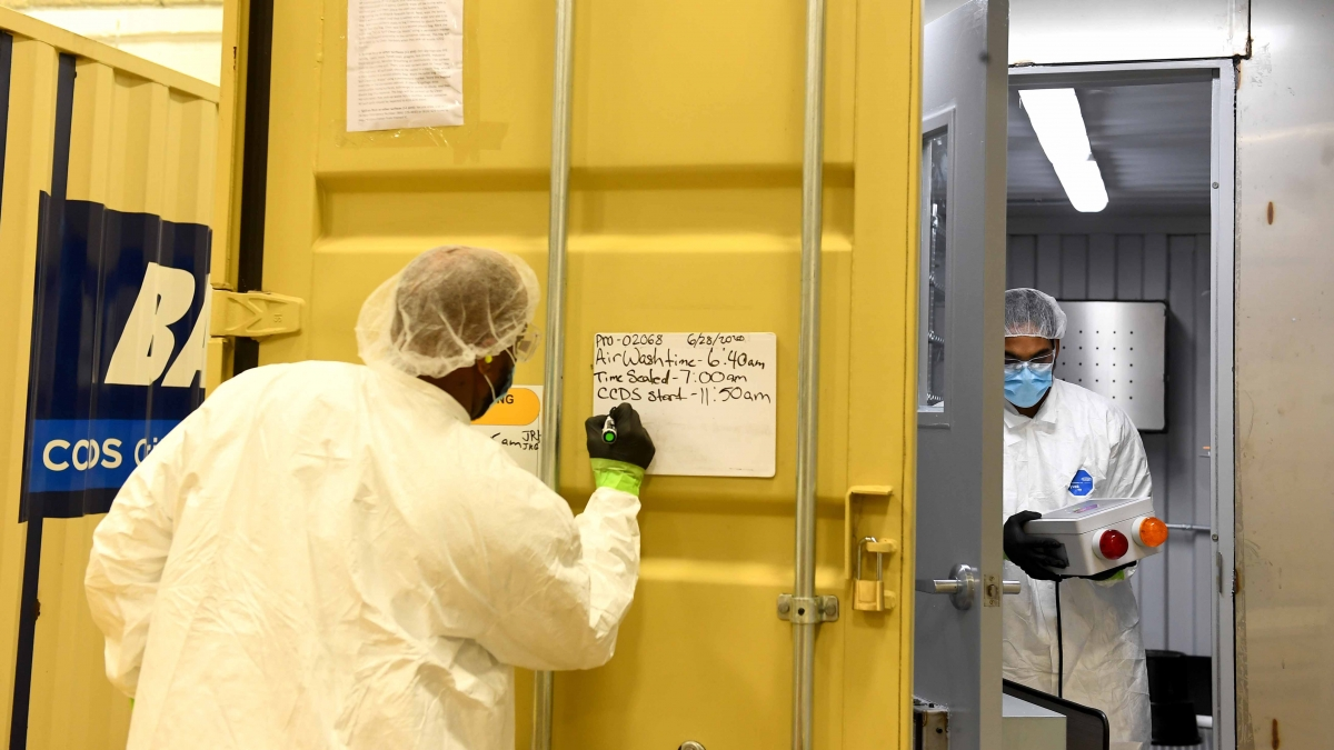 Decontamination Technician Troy Hubbard writes on a whiteboard that because humidity levels were high, the masks will take longer to clean after Courtney Walton took contamination meter readings on masks. MUST CREDIT: Washington Post photo by Katherine Frey.