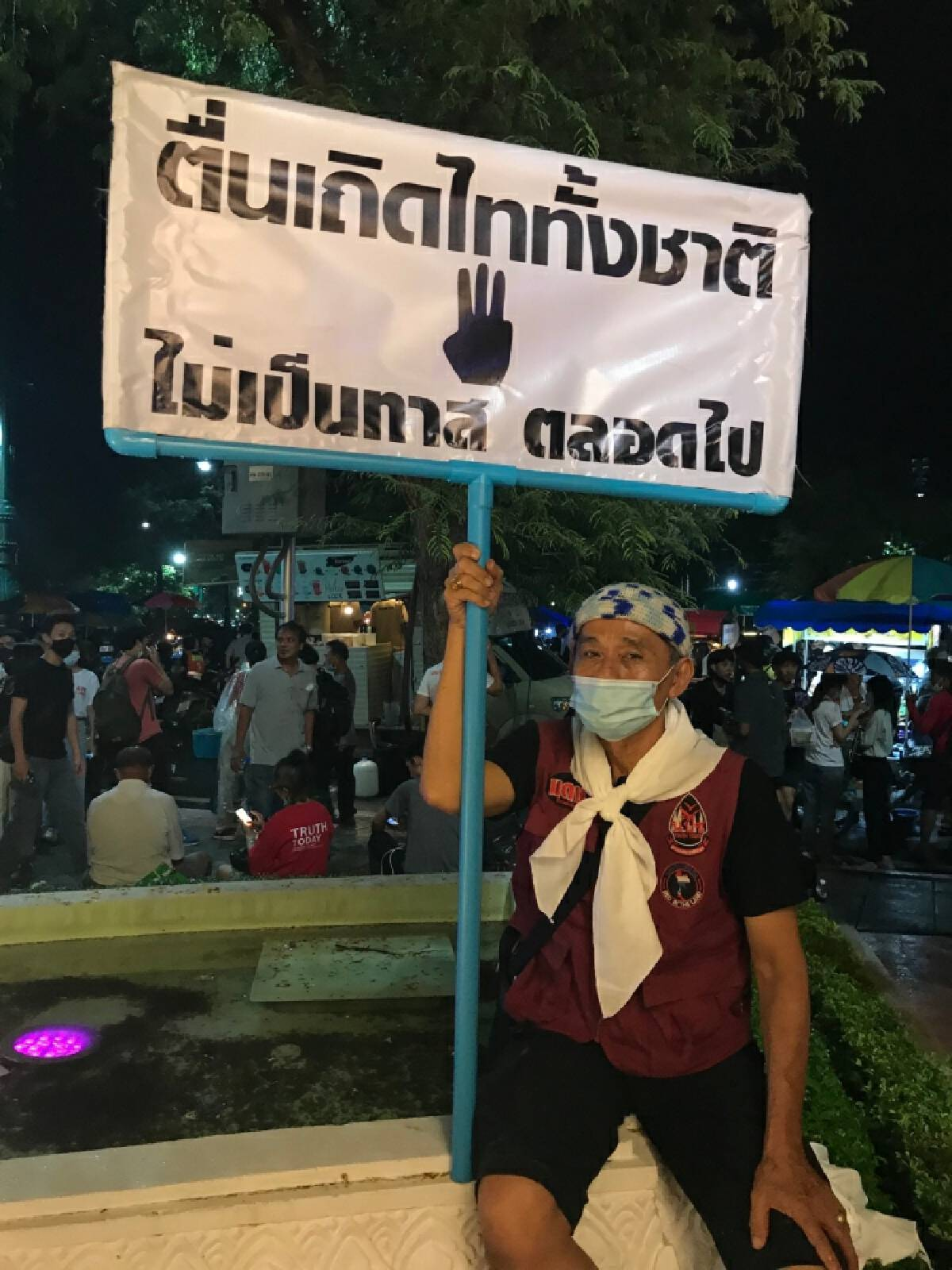 "Former red-shirt activist Bundit holds a banner reading ""Waking up Thais, no longer be slaves"" at the protest site on the night of September 19."