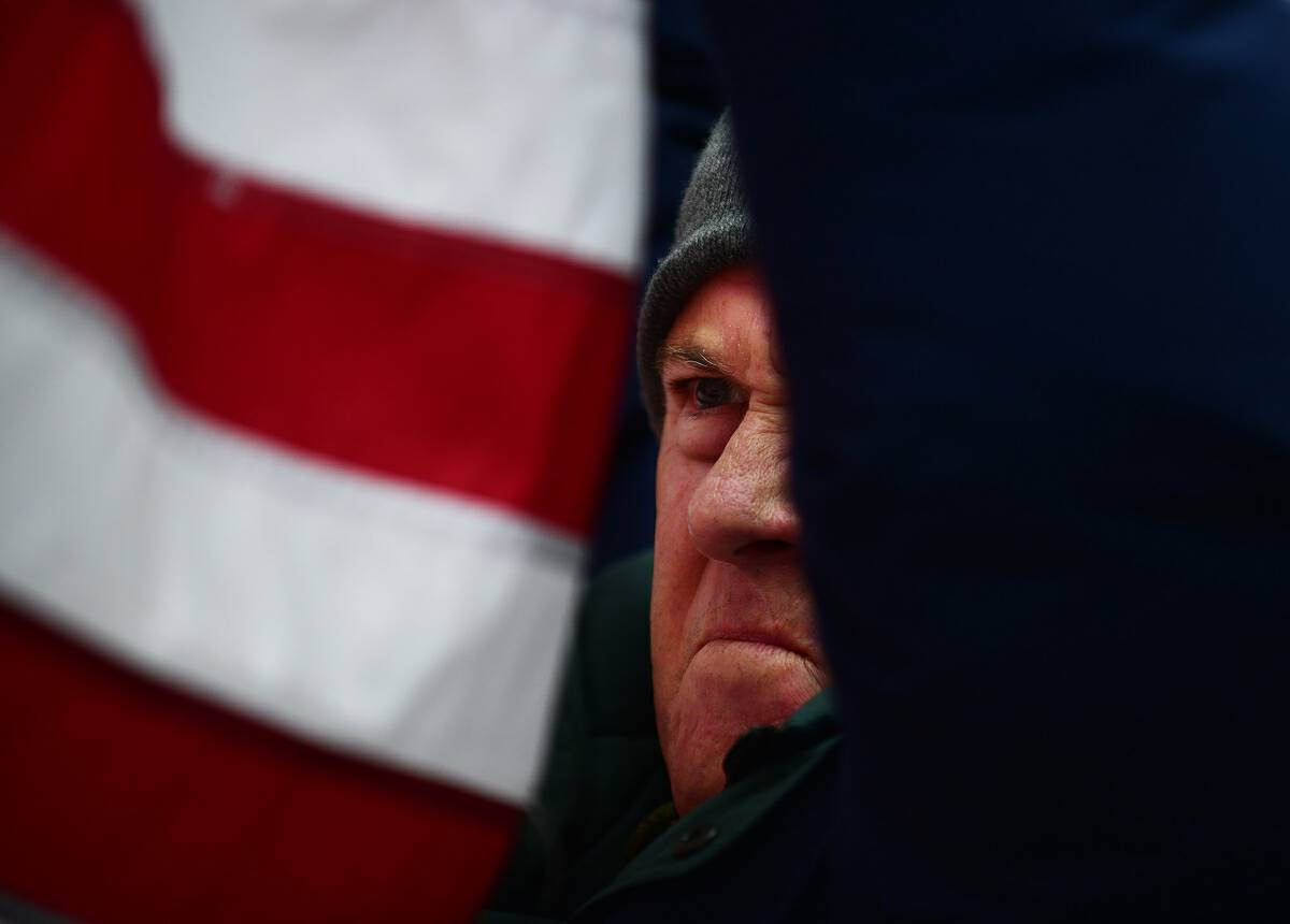 A supporter of President Donald Trump waves his flag while joining fellow supporters at Freedom Plaza to protest the results of the election. MUST CREDIT: Photo by Astrid Riecken for The Washington Post.