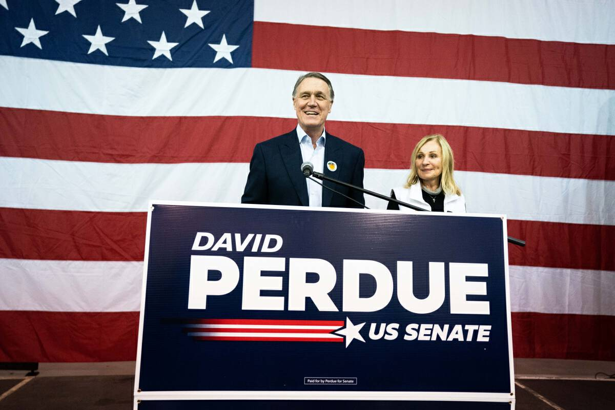 Republican Sen. David Perdue speaks during an airport rally in Atlanta on Dec. 14, with his wife, Bonnie. Perdue spent the last days of the election in quarantine after coming into contact with someone who contracted the coronavirus. MUST CREDIT: photo for The Washington Post by Kevin D. Liles.