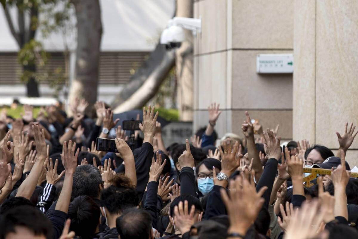 """Pro-democracy demonstrators make the gesture for the """"Five demands, not one less"""" motto outside the West Kowloon Magistrates Courts in Hong Kong on March 1, 2021. MUST CREDIT: Bloomberg photo by Paul Yeung"""