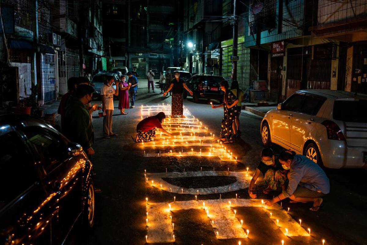 Residents light candles as part of a protest in Sanchaung to pray for those who have died during the protests. MUST CREDIT: photo for The Washington Post.