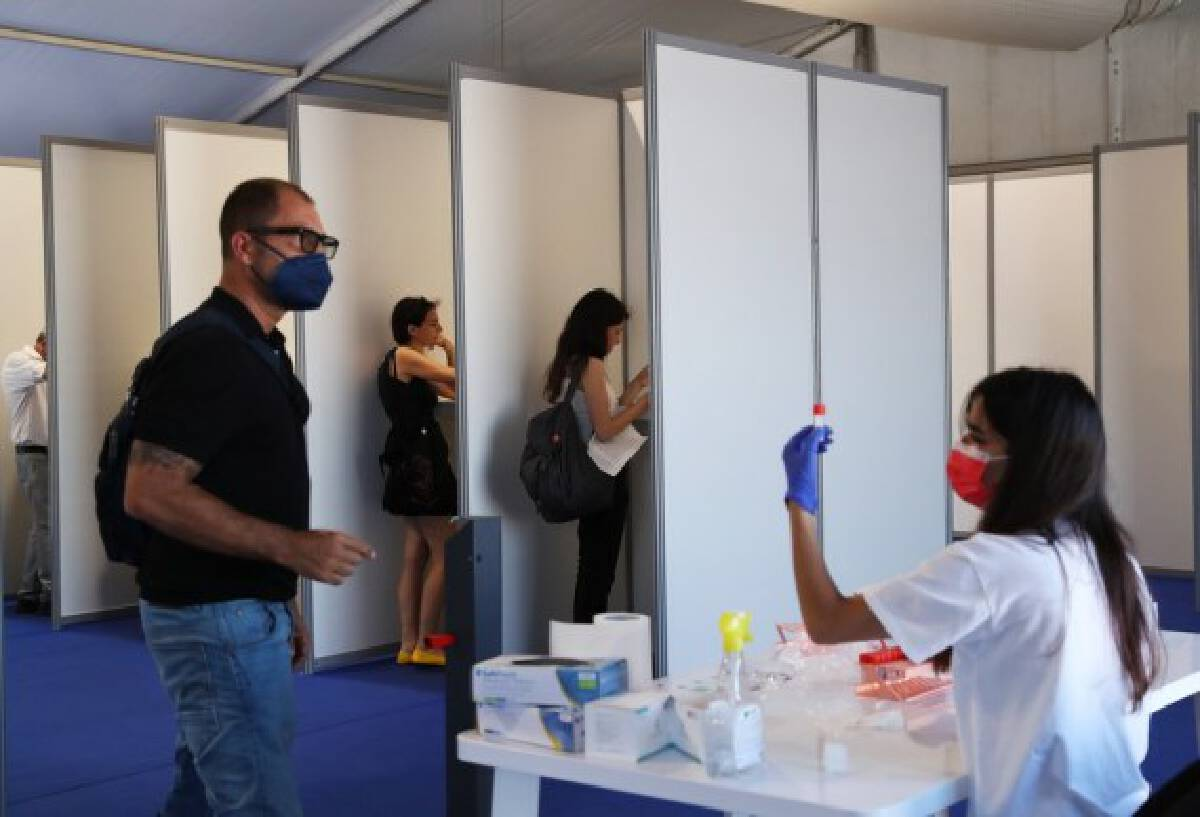 A medical staff member collects saliva samples for COVID-19 test at a tent ahead of the film festival in Cannes, southern France