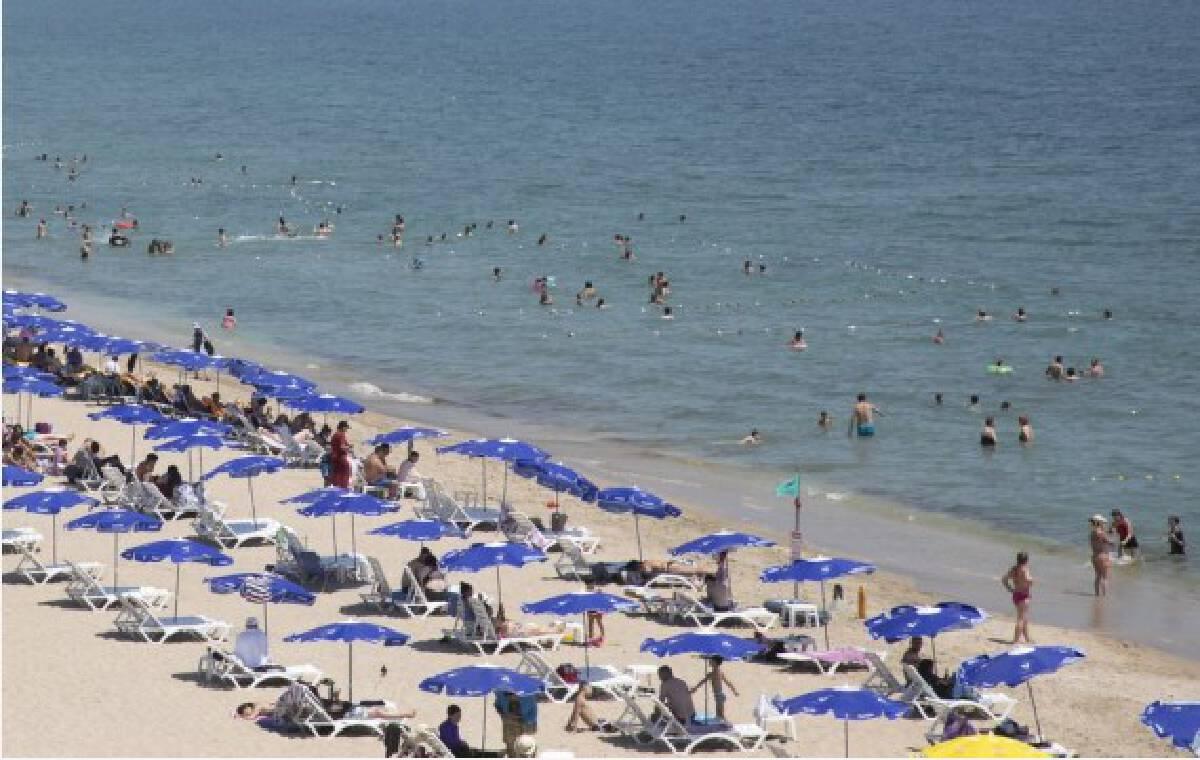 People enjoy leisure time at the seaside in Igneada, a small Turkish resort town of the Black Sea province of Kirklareli bordering Bulgaria, on July 20, 2021.