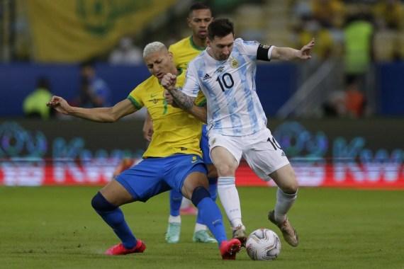 Lionel Messi (R) vies with Brazil's Richarlison (L).