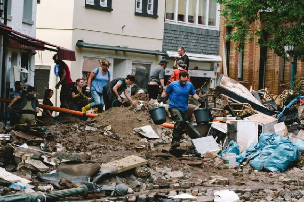 People clear a road damaged in floods in Bad Muenstereifel, western Germany, on July 17, 2021