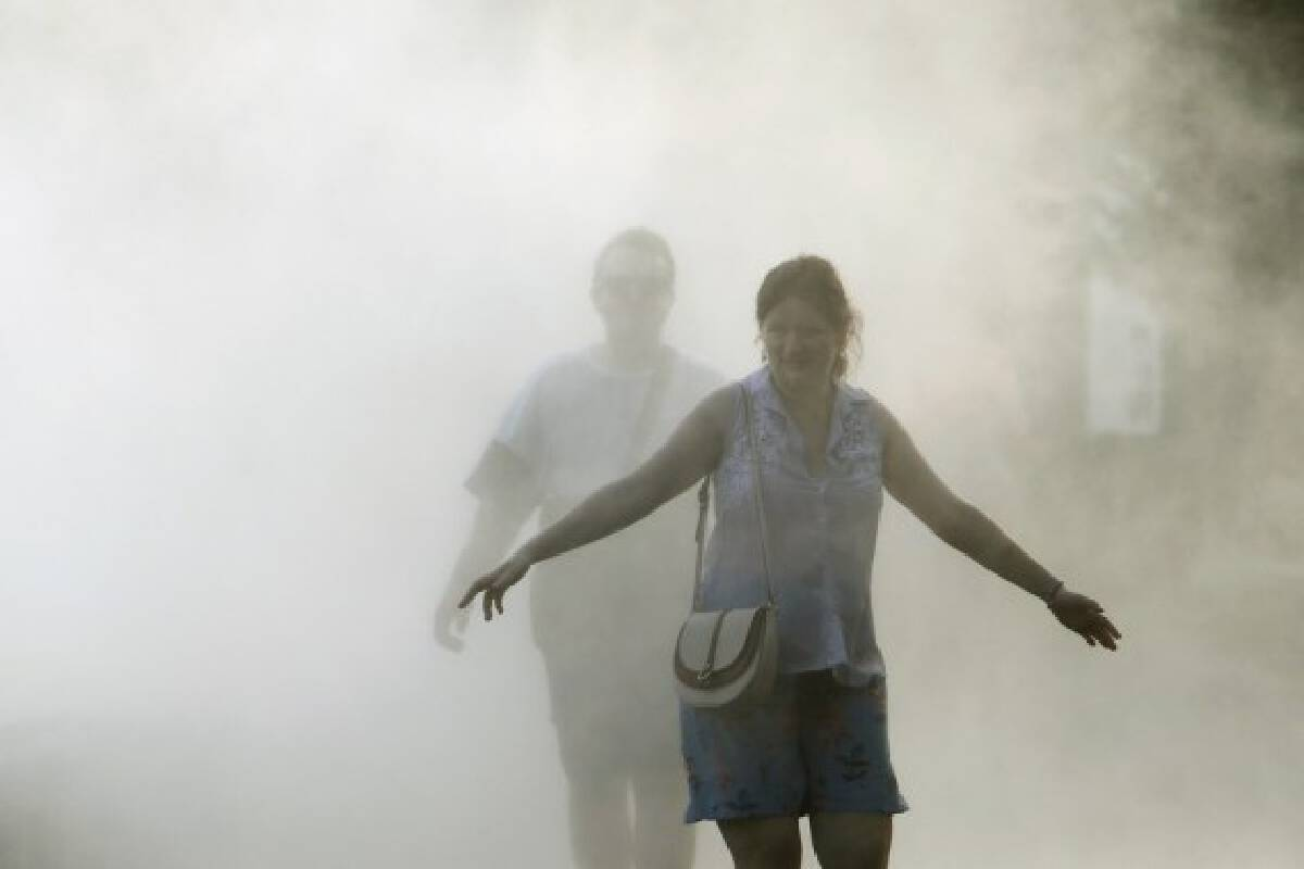 People cool off at a fountain during a hot day in downtown Bucharest, Romania, on July 28, 2021.