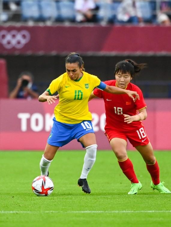 Marta (L) of Brazil vies with Wurigumula of China during Tokyo 2020 women's football group F match between China and Brazil in Miyagi, Japan, July 21, 2021.