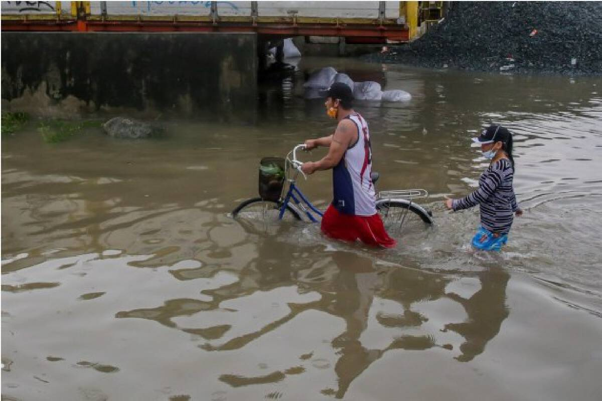 People wade through the flood water brought by heavy monsoon rains in Rizal Province, the Philippines, July 24, 2021.