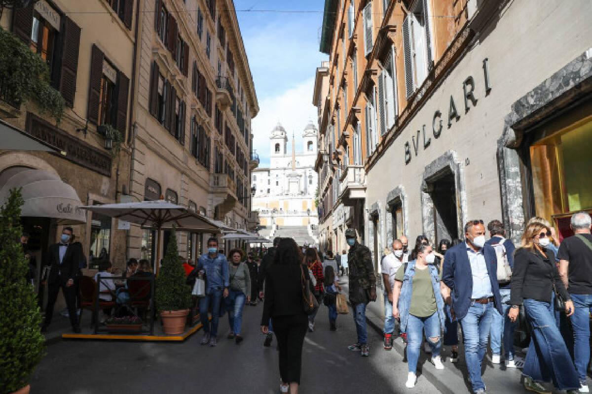 People walk on Via dei Condotti in Rome, Italy, May 15, 2021.