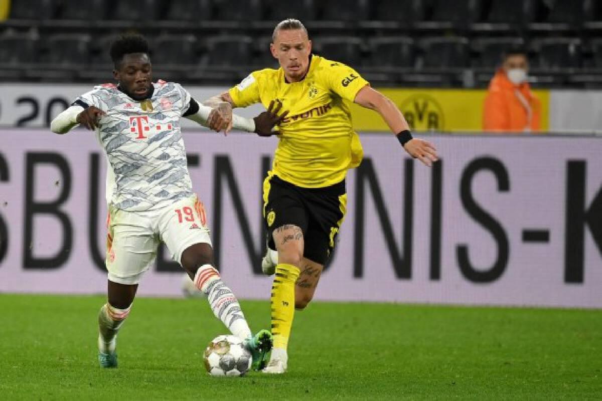 Marius Wolf (R) of Dortmund vies with Alphonso Davies of Bayern Munich during their German Supercup match in Dortmund, Germany, Aug. 17, 2021.
