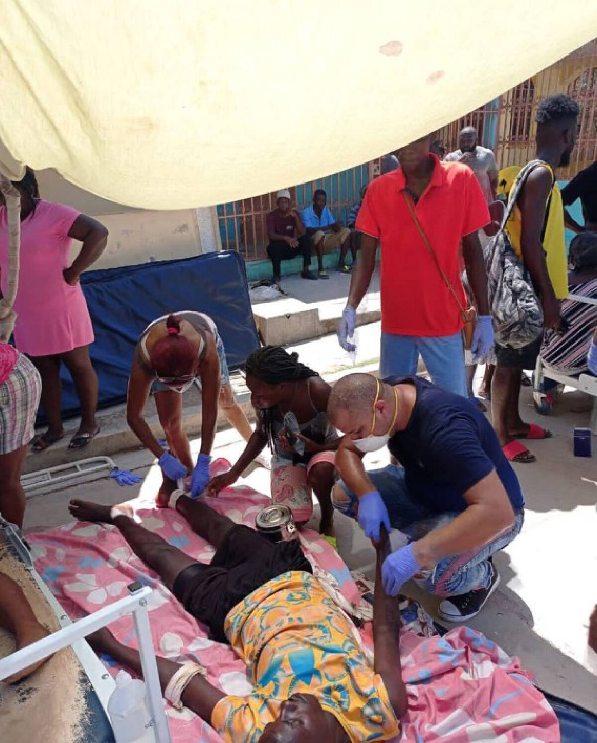 Photo taken with a mobile device shows members of the Cuban Medical Brigade helping an injured person after an earthquake in Jeremie, Haiti, Aug. 14, 2021.
