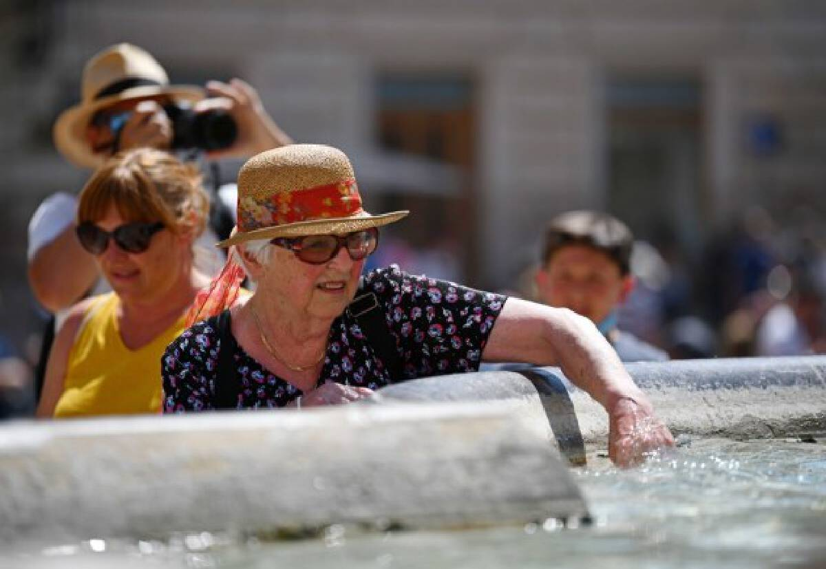 A tourist cools off by a fountain near the Pantheon in Rome, Italy, Aug. 12, 2021.