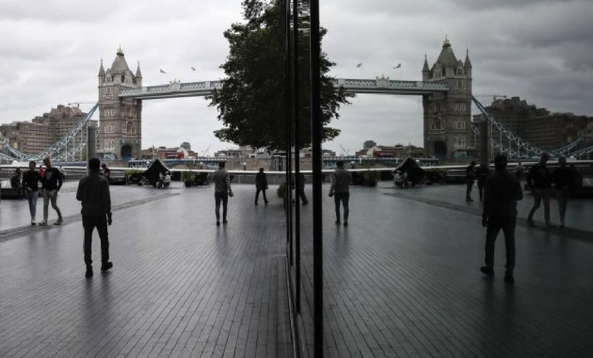 People walk near the Tower Bridge in London, Britain, on Aug. 13, 2021.