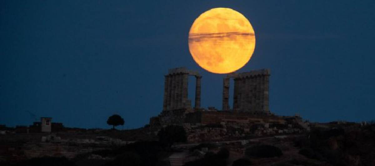 A full moon is seen over the Temple of Poseidon at cape Sounion, some 70 km southeast of Athens, Greece, on Aug. 21, 2021.