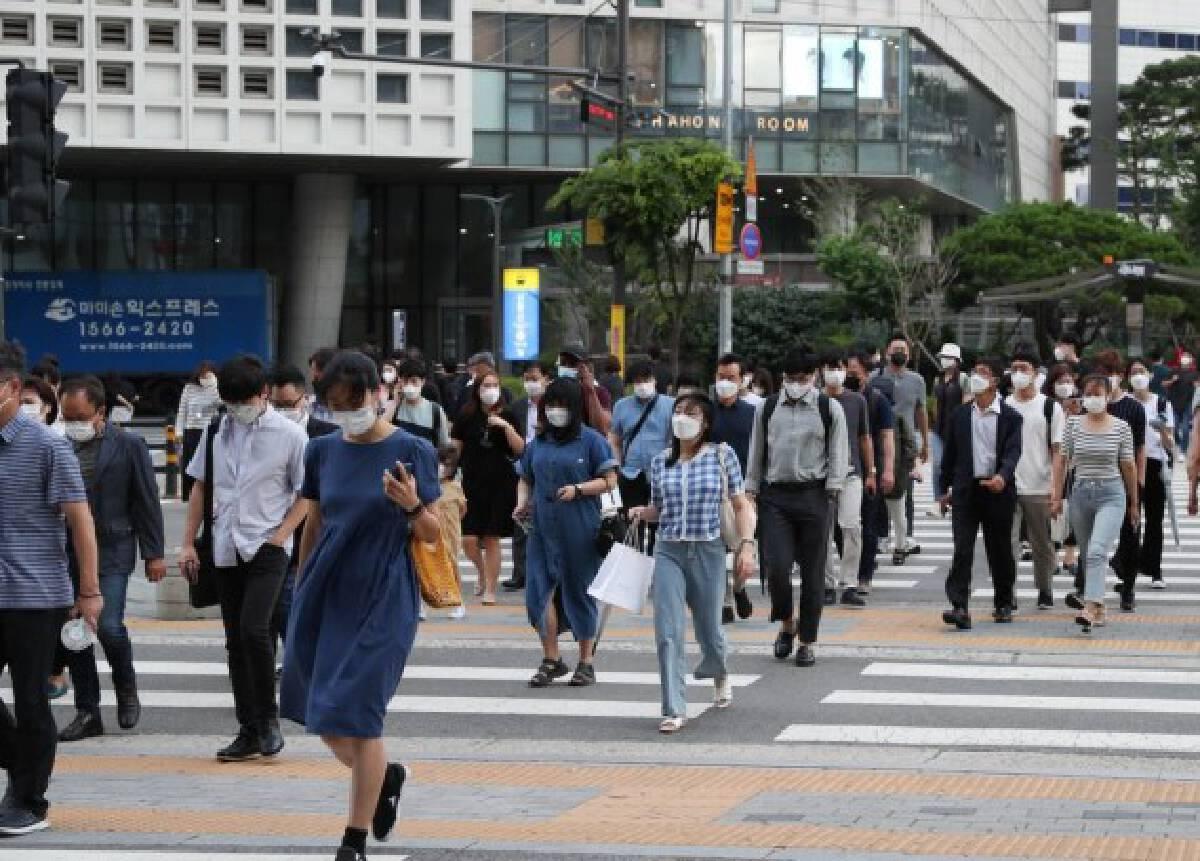 People wearing face masks walk across the street near Yongsan Station in Seoul, South Korea, July 8, 2021.