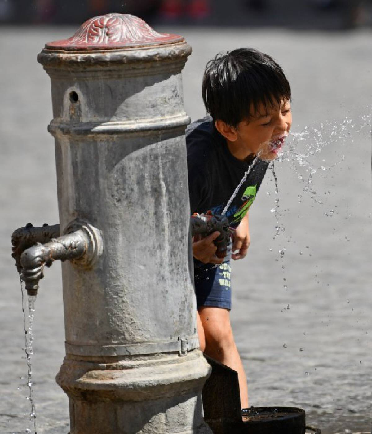 A boy refreshes himself with the tap water in Rome, Italy, Aug. 12, 2021.