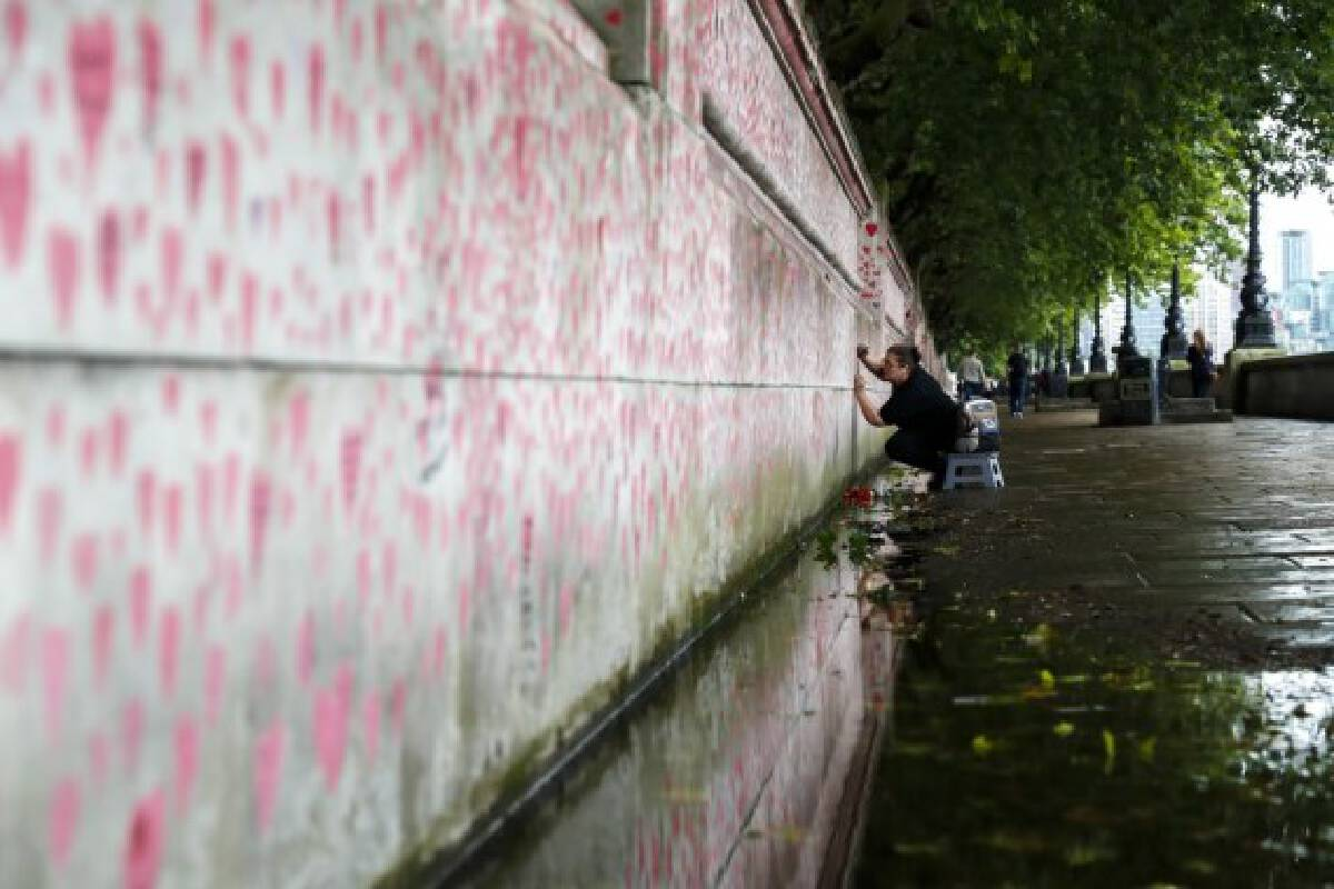 A woman draws a red heart on the National COVID Memorial Wall in London, Britain, Aug. 9, 2021.