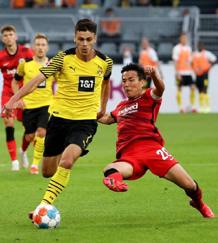 Giovanni Reyna (L) of Dortmund vies with Hasebe Makoto of Frankfurt during a German Bundesliga match in Dortmund, Germany, Aug. 14, 2021.