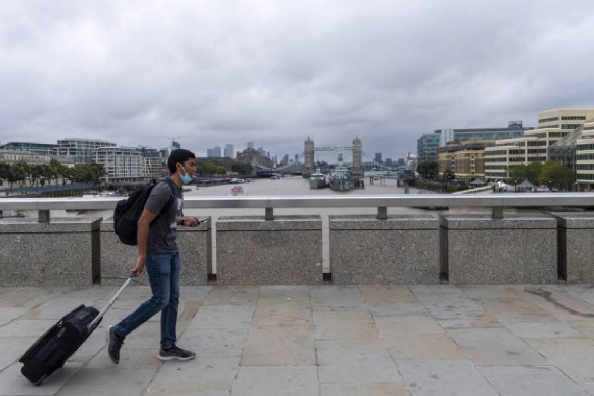 A man walks across London Bridge in London, Britain, Aug. 30, 2021.