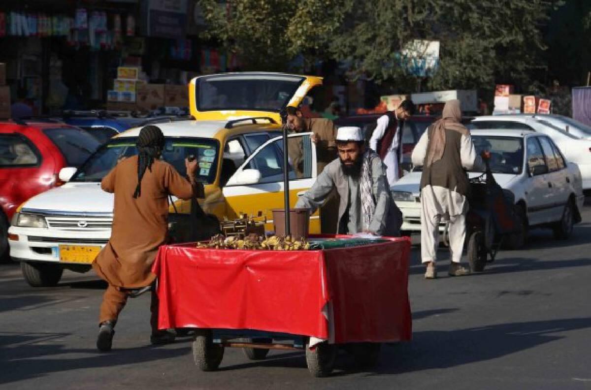 Vendors push their handcarts on a street in Kabul, capital of Afghanistan, Sept. 15, 2021. (Photo by Kabir/Xinhua)