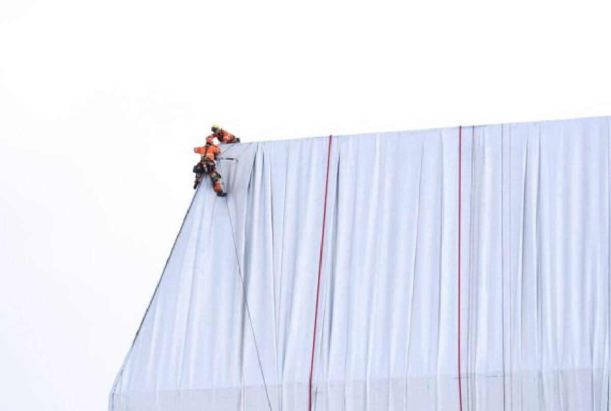 Workers put the finishing touches on the wrapped Arc de Triomphe in Paris, France, on Sept. 16, 2021. (Xinhua/Gao Jing)